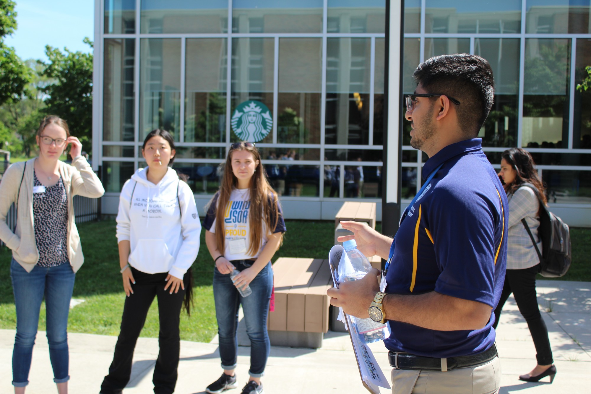 A staff member providing students with a tour of campus