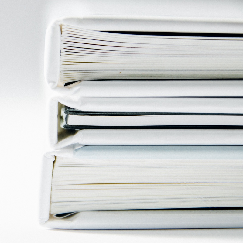 Three vertically stacked binders, filled with paper, side view to camera. White background