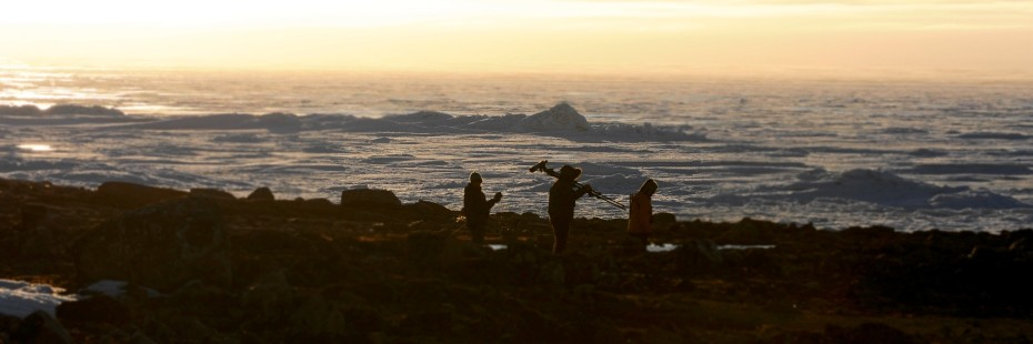 Three unidentified UWindsor researchers trek across a rocky shoreline at sunset, carrying varous measuring equipment.