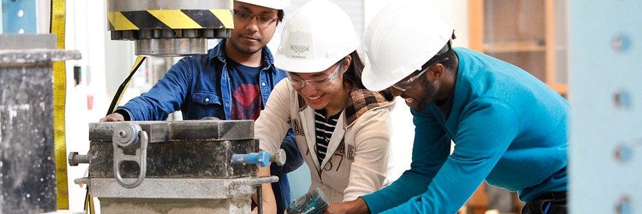 image of three people with safety gear working on civil engineering equipment