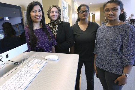 Women standing by computer monitor