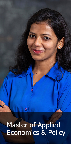 Lady in blue shirt arms crossed and smiling at camera