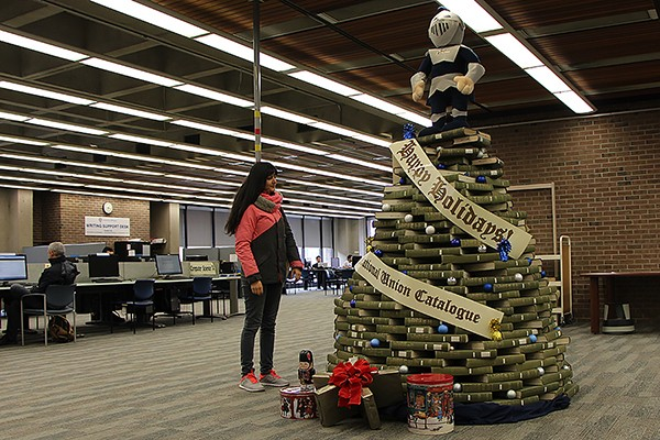A student admires a holiday tree made of volumes stacked by the Leddy Library's resident elves.