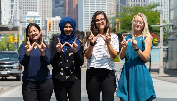 "Group of students downtown making ""W"" signs with their hands"