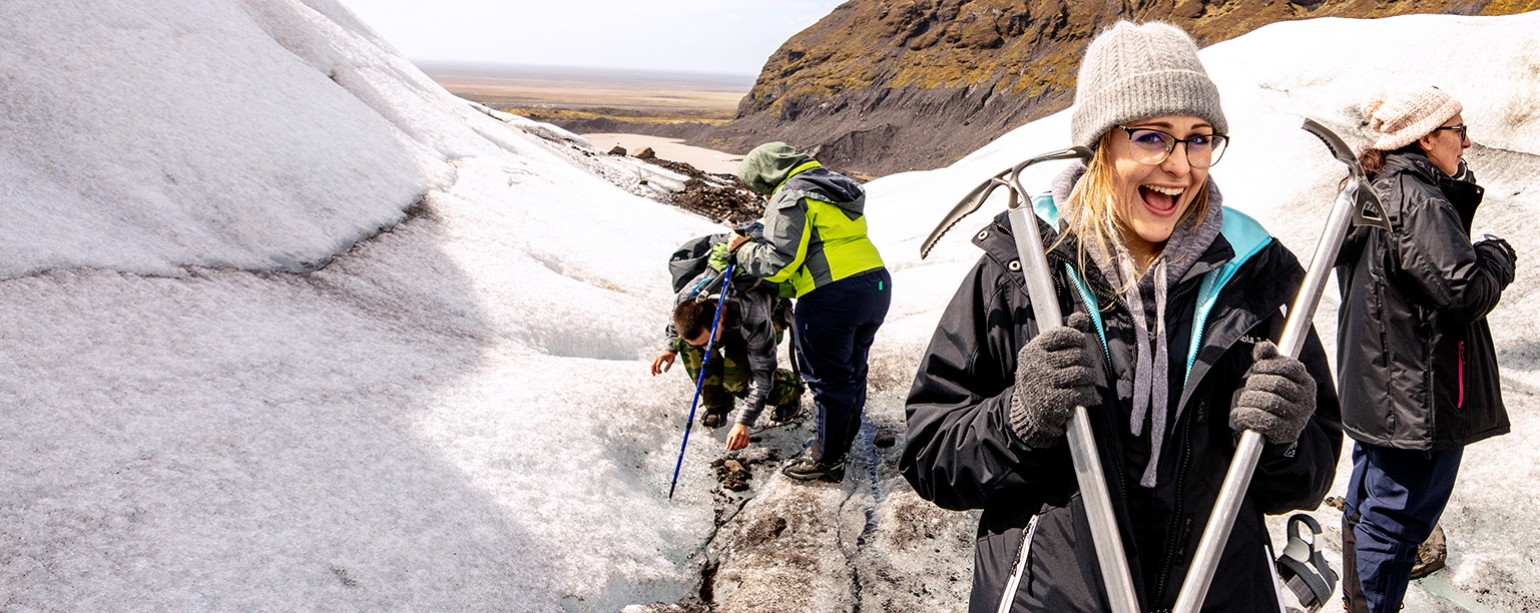 Student holding pickaxe during field research in Iceland