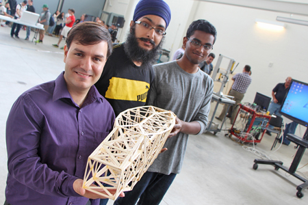 Students hold popsicle stick bridge model