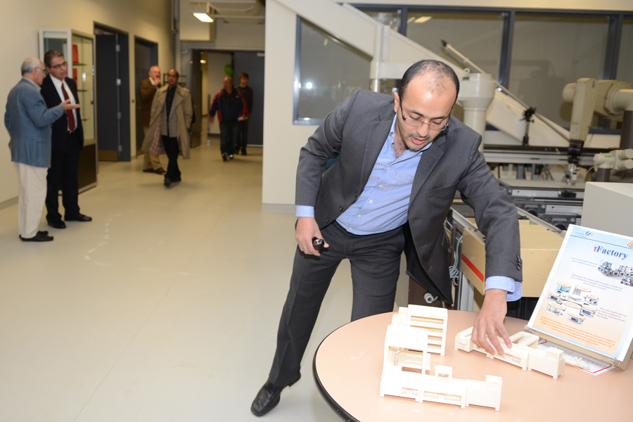 professor Ahmed Azab adjusts scale model on table