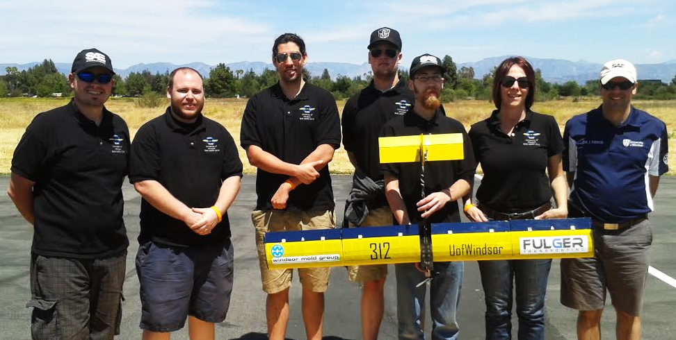 UWindsor team holding their successful aircraft deign at SAE Aero Design West Collegiate Competition. From left to right: Andrei Tineghe, Justin Abbott, Mitchell Campbell, David Carrick , Kevin Brooks, Richelle Dolan, and Faculty Advisor Jeff Defoe .