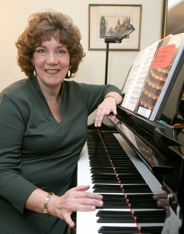 Catherine McKeever sitting at her piano in her teaching studio