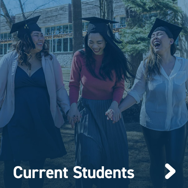 Three students laughing and walking towards camera