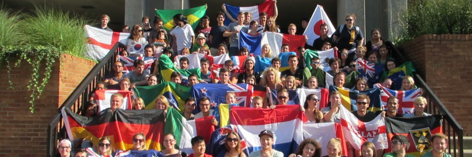 Group photo of incoming exchange students on stairs with their flags.