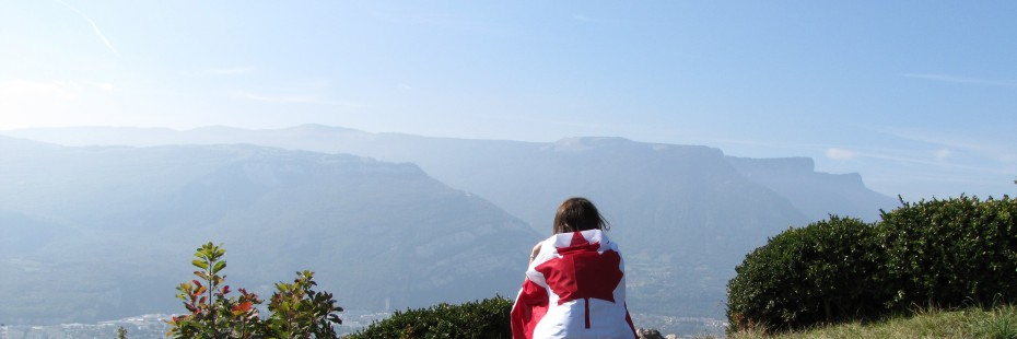 Exchange student sitting on a mountain with a Canadian flag