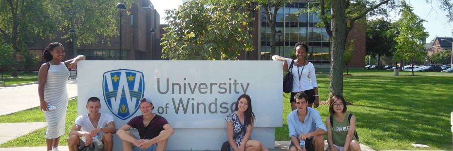 Group of students sitting in front of the UWindsor sign