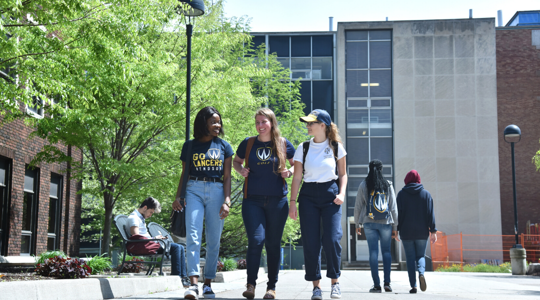 three UWindsor students walking outside of the CAW student centre