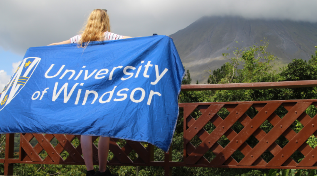 A student on exchange holding up the University of Windsor flag