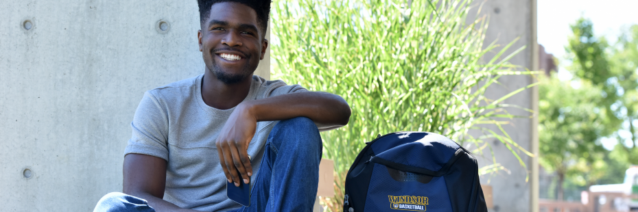 Student sitting on the grass with UWindsor Basketball backpack