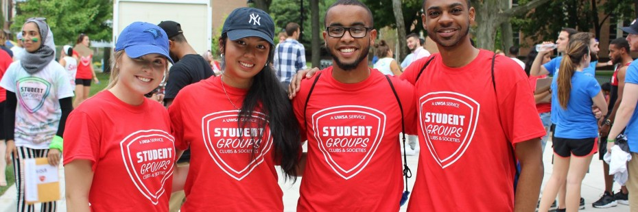 Four students standing together wearing red t-shirts that say student groups on them
