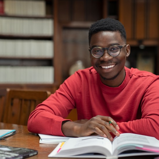 Image of Black student studying in a library setting