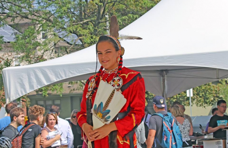 A girl in ceremonial dress is shown as part of the Turtle Island Walk day of celebration.