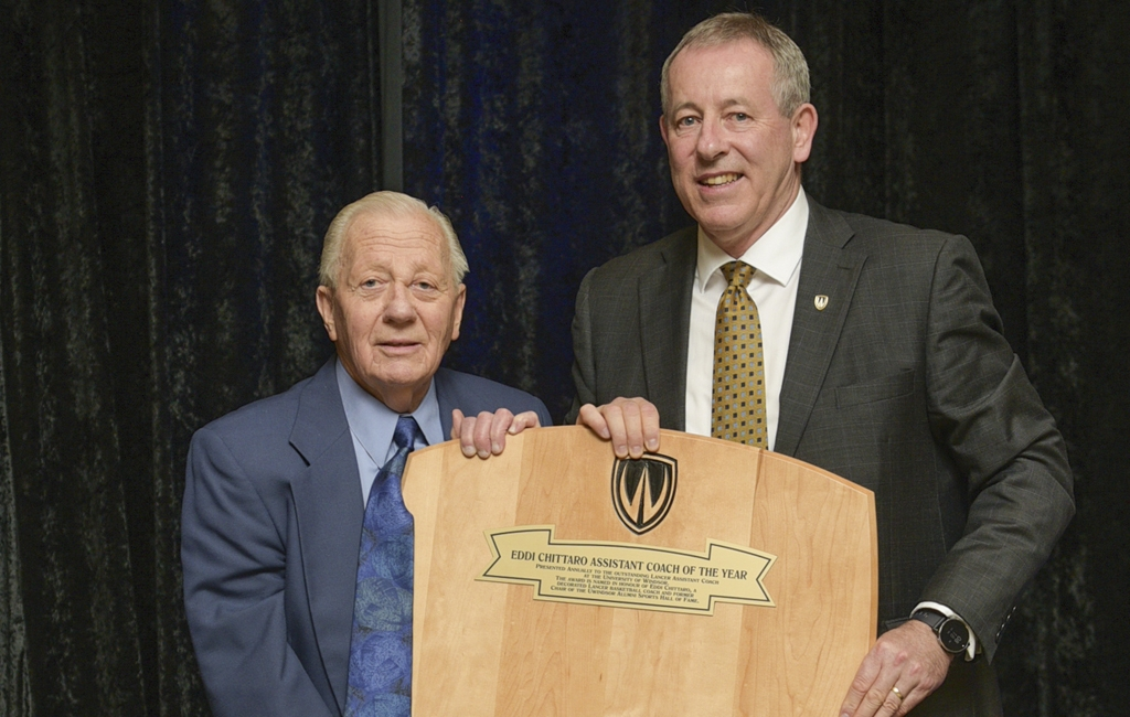 Eddi Chittaro, BA '55, MA '58 (left) former chair, Alumni Sports Hall of Fame committee, is honoured for his years of service by Athletics' Director Mike Havey. (Ted Kloske photo)
