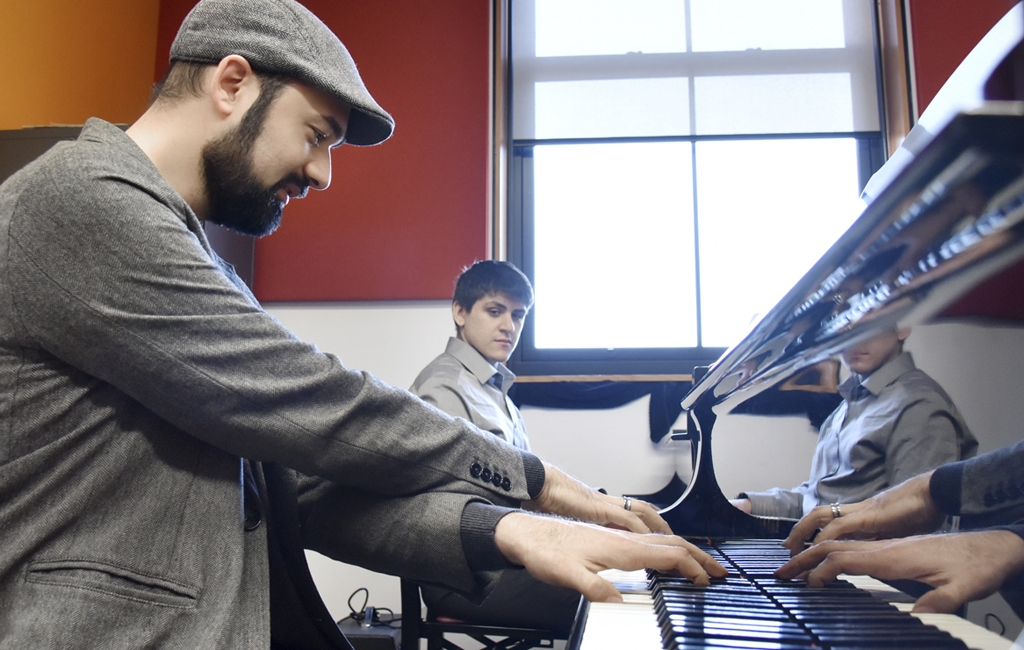 "Jazz/contemporary piano instructor Michael Karloff demonstrates ""cross hand"" technique to his student Alex Aideira-Leite"