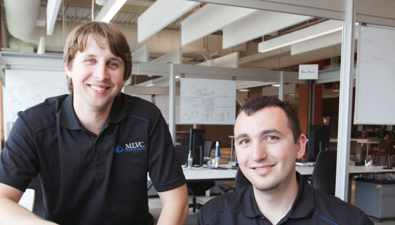 Recent graduates Matthew Lapain and Vincent Colussi are shown working at the Epic Innovation office in the Joyce Entrepreneurship Centre at the University of Windsor.