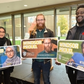 UWindsor students Amal Siddiqui, Max Arvidsson, and David Adelaja pose with mock-ups of billboards bearing their images as part of the Windsor Proud campaign
