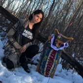 Andrea Landry is shown in a snowy, wooded area, with her baby, both in traditional Aboriginal attire.