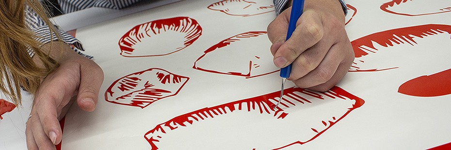 Student creating an image by scraping off colour coating