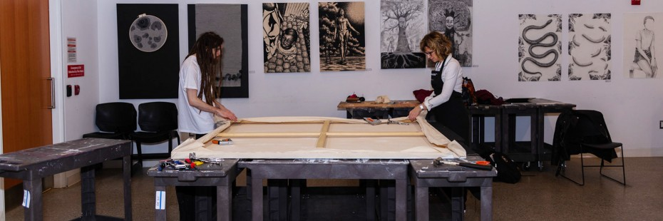 Lisa Baggio and student prepare a large canvass in the studio