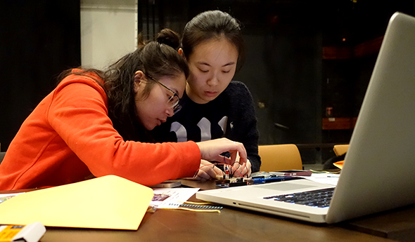 2 students working with an arduino