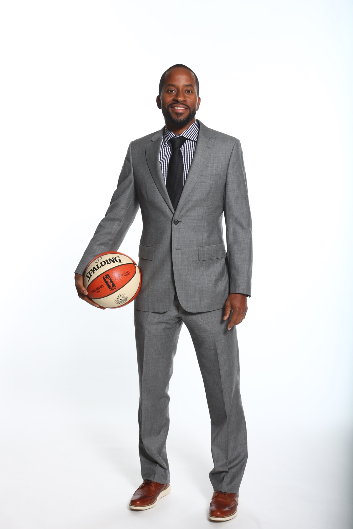Full-body photo of Sefu Bernard in a grey suit, holding a basketball